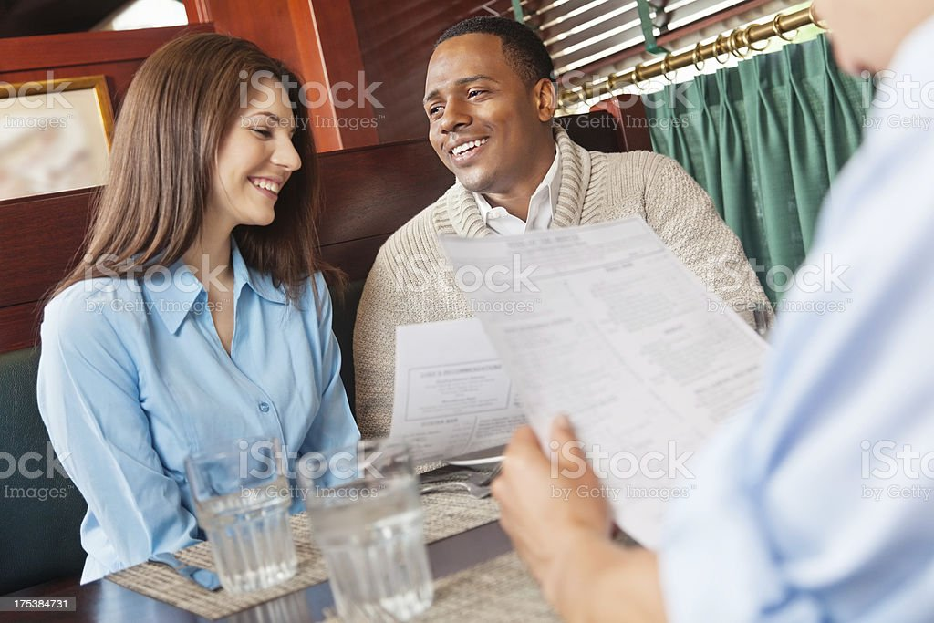 Friends reading the menu in a restaurant booth royalty-free stock photo