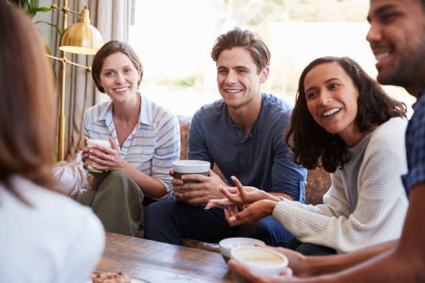 Friends relaxing around a table at a coffee shop, close up stock photo