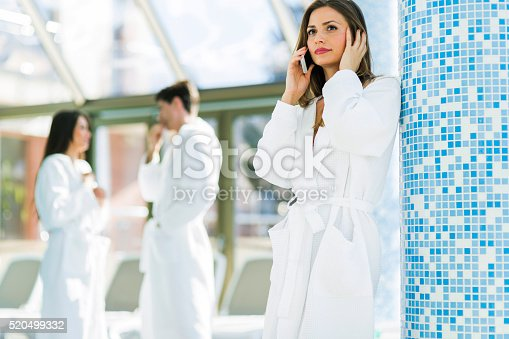 610769340istockphoto Friends relaxing in a spa next to a swimming pool 520499332