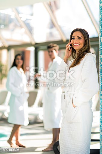 610769340istockphoto Friends relaxing in a spa next to a swimming pool 520499396