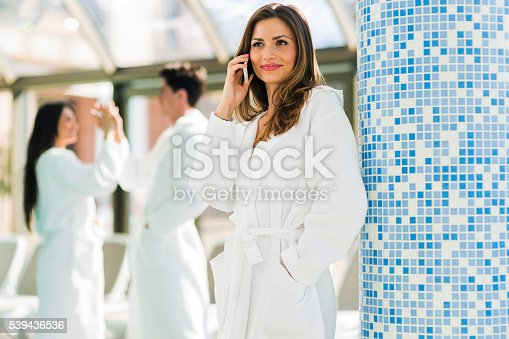 610769340istockphoto Friends relaxing in a spa next to a swimming pool 539436536