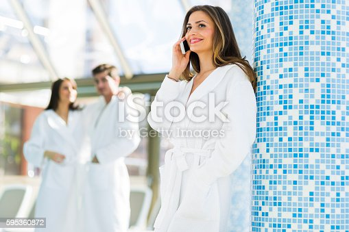 610769340istockphoto Friends relaxing in a spa next to a swimming pool 595360872