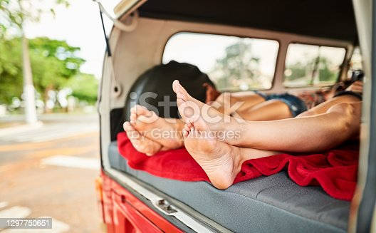 Shot of a two women friends lying inside a retro van, focus on feet