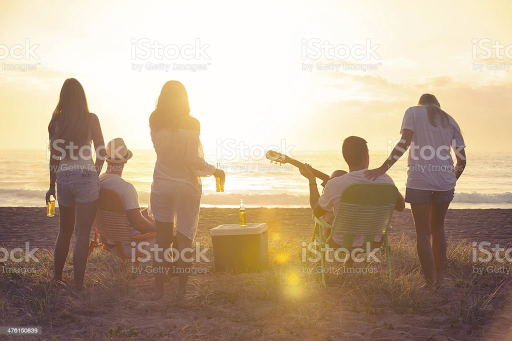 Friends relaxing on a beach at sunset royalty-free stock photo