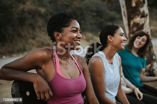1051098428istockphoto Friends relaxing on a park bench 1030689018