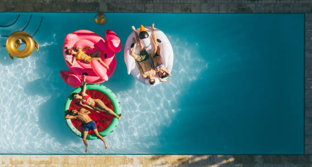 Friends relaxing on inflatable mattresses in pool Aerial view of young people on summer vacation enjoying on fun inflatable floats in swimming pool. Group of friends relaxing on air mattresses in pool. poolside stock pictures, royalty-free photos & images