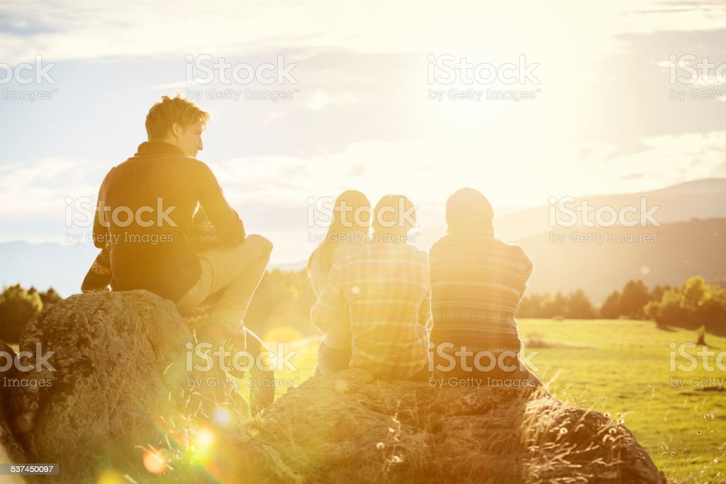 Friends relaxing on rock at field stock photo