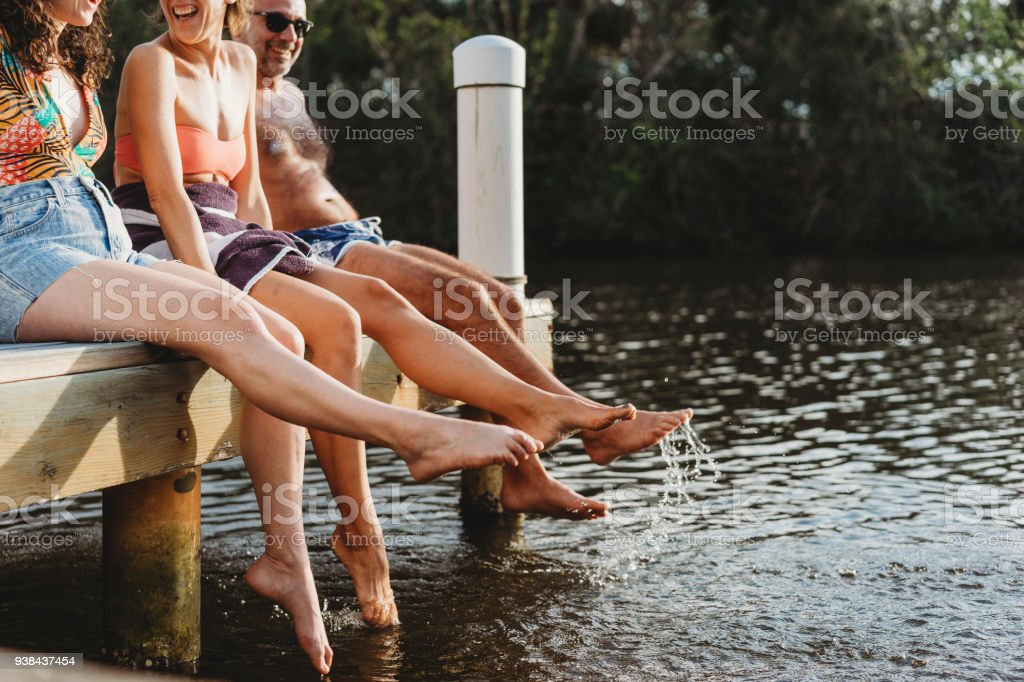 Friends relaxing on the pier stock photo