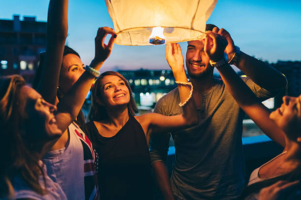 Friends releasing paper lantern for New Year Happy friends on a rooftop party holding a sky lantern indochina stock pictures, royalty-free photos & images