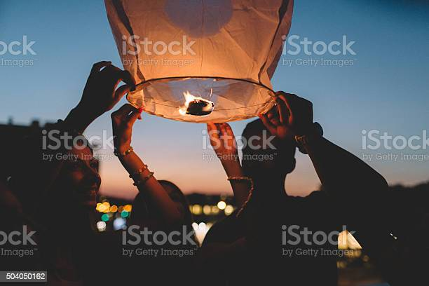 Friends releasing paper lantern in the sky at night picture id504050162?b=1&k=6&m=504050162&s=612x612&h=v13tuecuzp7tosgb6riimjbgyubj7 icewp98t8pifg=