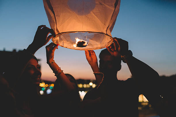 amigos liberando luminária de papel no céu, à noite - lanterna - fotografias e filmes do acervo