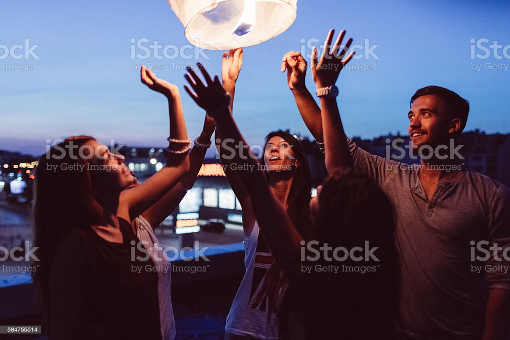 Friends releasing paper lantern in the sky at night stock photo