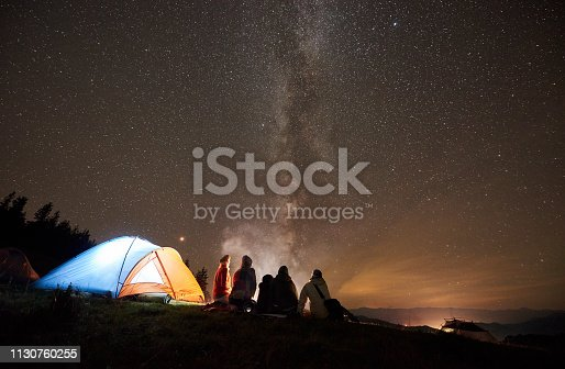 678554980 istock photo Friends resting beside camp, campfire under night starry sky 1130760255