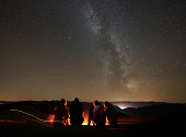 Back view group of four young friends hikers resting together around bonfire near camp and tourist tent at night in the mountains. On background beautiful night starry sky full of stars and Milky way.