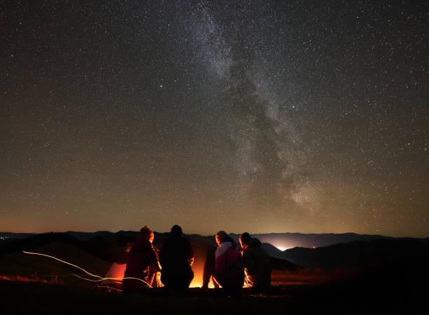friends resting beside camp, campfire under night starry sky - falò foto e immagini stock