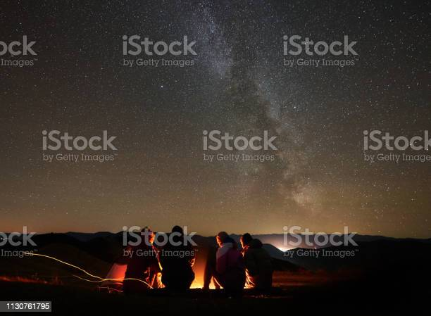 Photo of Friends resting beside camp, campfire under night starry sky