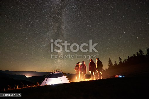 Night summer camping in the mountains. Back view of happy friends hikers having a rest together around campfire near glowing tourist tent under amazing night starry sky full of stars and Milky way.