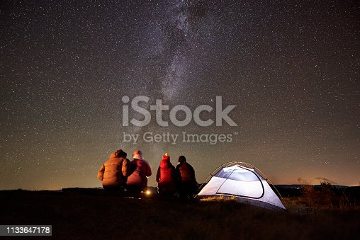 678554980 istock photo Friends resting beside camp, campfire under night starry sky 1133647178