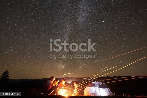 678554980 istock photo Friends resting beside camp, campfire under night starry sky 1133647179