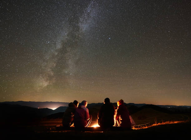 Friends resting beside camp, campfire under night starry sky Night summer camping in the mountains. Back view group of four friends tourists sitting on a bench made of logs together around campfire under amazing night starry sky full of stars and Milky way. bonfire stock pictures, royalty-free photos & images