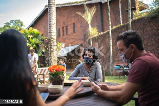 Friends reunited in the backyard, talking and using smartphone