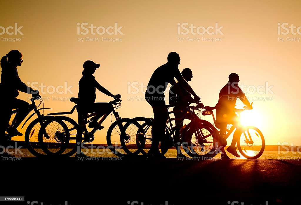 Friends riding bicycles at sunset stock photo