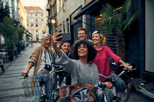 Friends Riding Bicycles In A City. Cycling in pedestrian zone and making selfie.