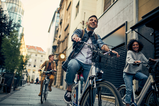 Group of Friends Riding Bicycles In A City. Cycling in pedestrian zone and smiling.