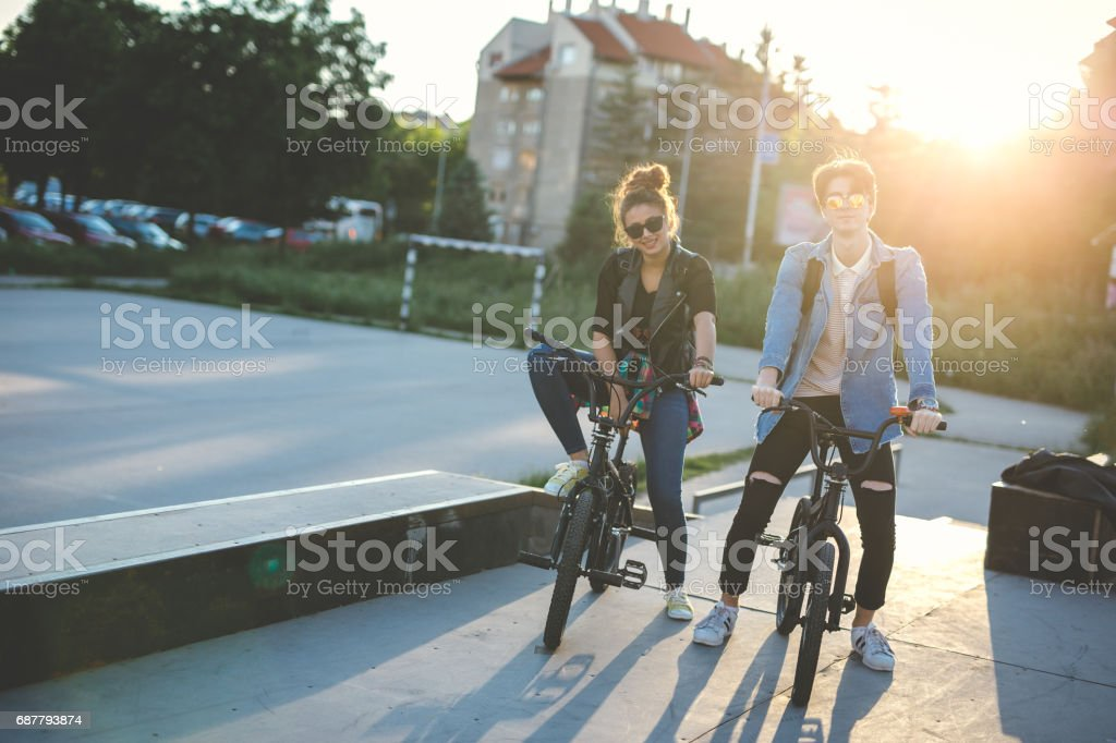 Friends riding bike in the skate park stock photo