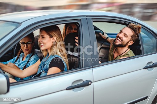 972962180 istock photo Friends riding in the car with open windows and laughing 969927574