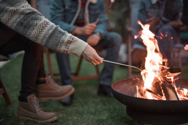 Friends roasting marshmallows on fire pit stock photo