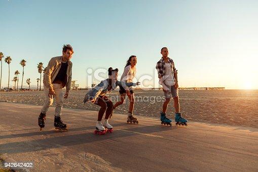 Friends roller skating on the boardwalk in Venice Beach - Santa Monica promenade - Los Angeles, USA
