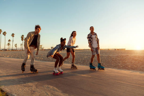 Friends roller skating on the boardwalk in Venice Beach - Santa Monica promenade - Los Angeles, USA Friends roller skating on the boardwalk in Venice Beach - Santa Monica promenade - Los Angeles, USA boardwalk stock pictures, royalty-free photos & images