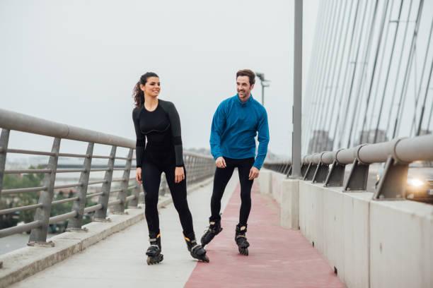 Friends roller skating on the bridge stock photo