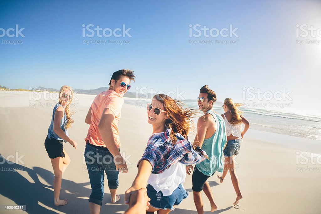Friends running along the beach stock photo