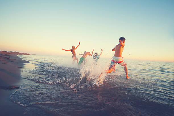 Friends running in to sea foto