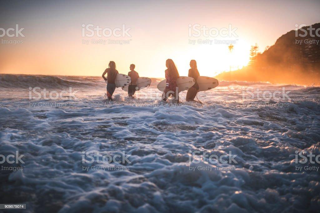 Freunde, die laufen in den Ozean mit ihren Surfbrettern – Foto