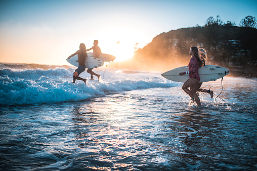 Friends running into the ocean with their surfboards