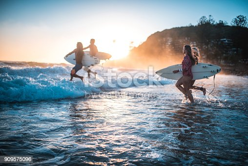 istock Friends running into the ocean with their surfboards 909575096
