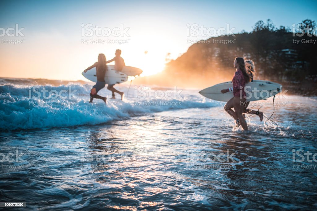 Friends running into the ocean with their surfboards stock photo