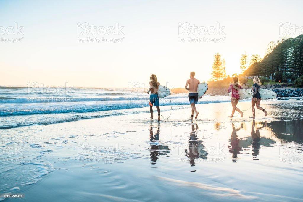 Friends running into the water with surfboards at sunset stock photo