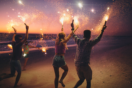 471113366 istock photo Friends running on a beach with fireworks 471881684