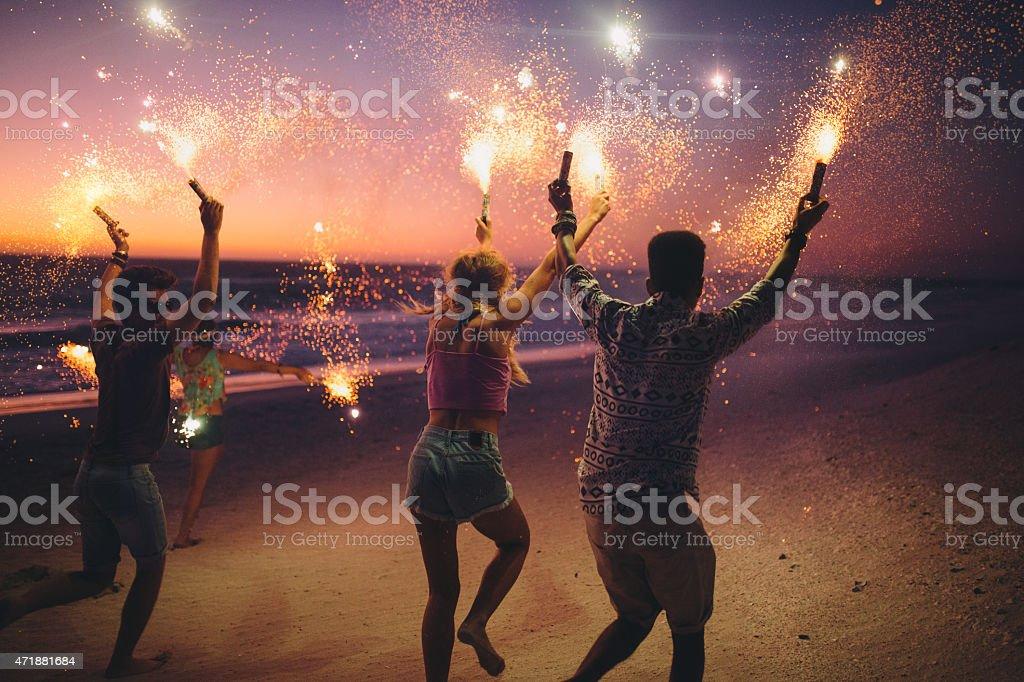 Amici in esecuzione su una spiaggia con fuochi d'artificio - foto stock