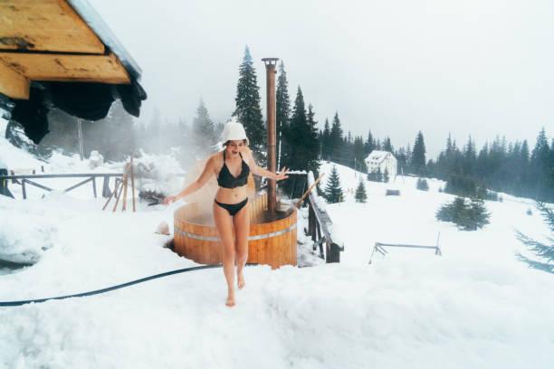 Amis en cours d'exécution sur la neige après avoir lavé dans le bain à remous en plein air - Photo