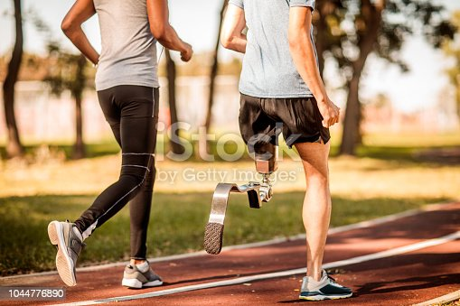 Rear view of unrecognizable multi-ethnic male friends running together on the running track. One of them has prosthetic leg.