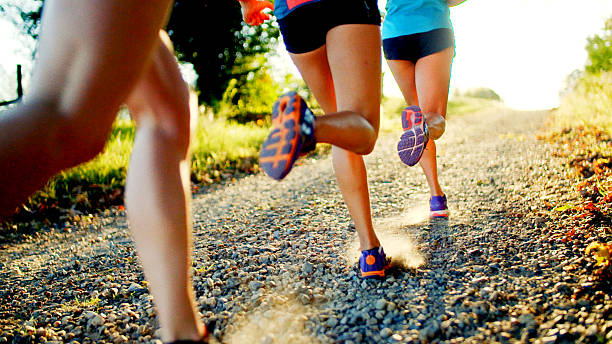 Friends Running Group of women running down gravel road. women's track stock pictures, royalty-free photos & images