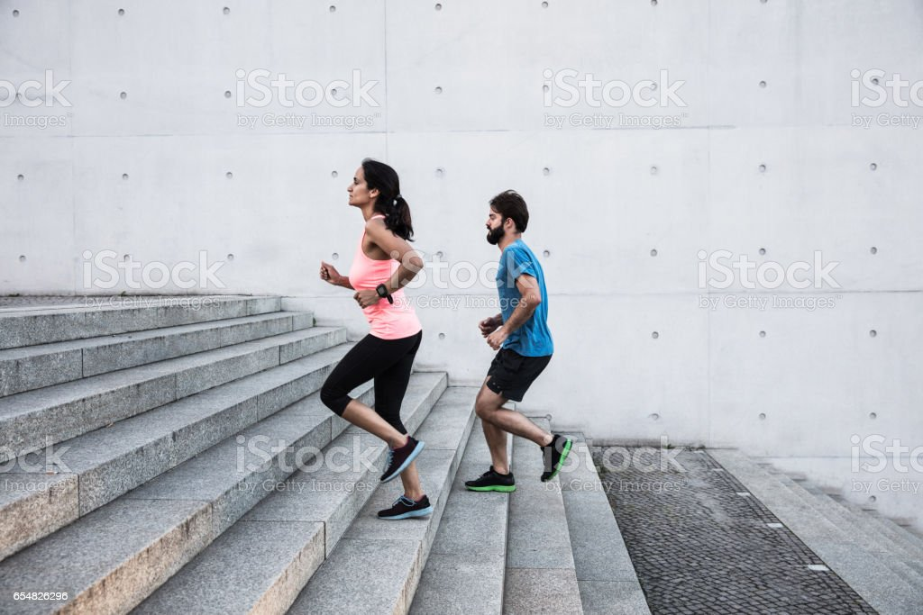 friends running steps up in urban setting stock photo