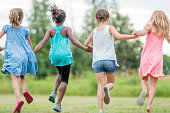 A multi-ethnic group of elementary age girls are holding hands and are running through the grass.