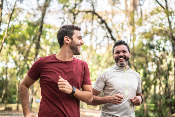 Friends running together in a park Friends running together in a park fitness tracker stock pictures, royalty-free photos & images
