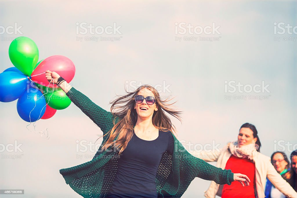 Friends running with balloons, carefree, fun, enjoyment stock photo